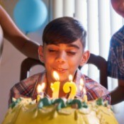 "A birthday cake with a ""12"" on the top and a boy blowing out the candles."