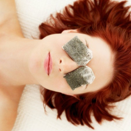 Woman with tea bags on her eyes