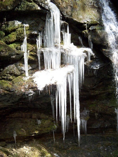 Icicles on rocks near small waterfall.