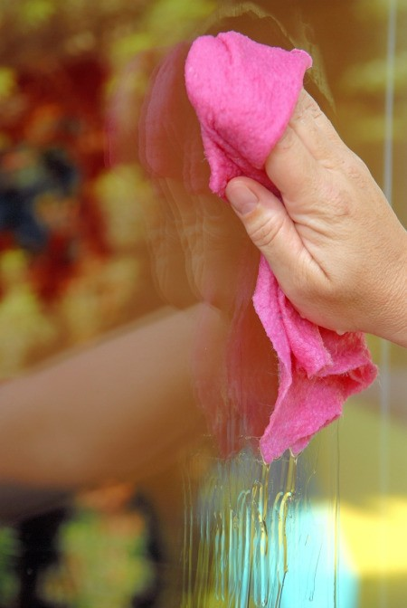 A person cleaning a window with a rag.