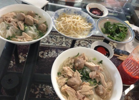 Homemade Vietnamese pho on a table, ready to eat.