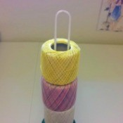 Several rolls of crochet thread on a toilet paper holder.
