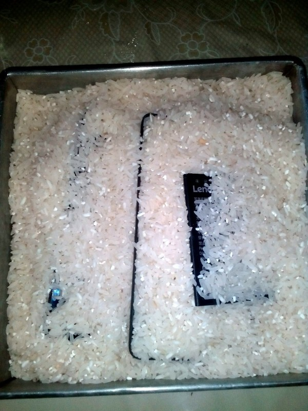 A smartphone being buried in rice to dry it out.
