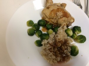 A plate of simmered chicken with rice and vegetables.