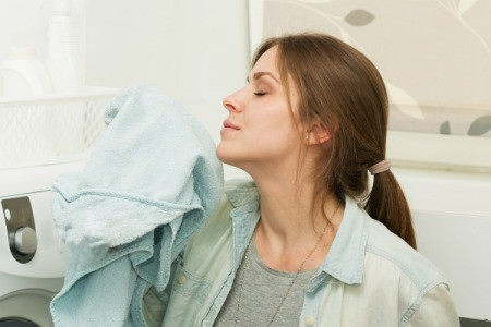A woman smelling fresh laundry.