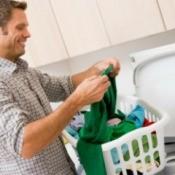 A man putting clothes into a washing machine.
