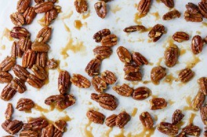A sheet pan with caramel covered nuts.