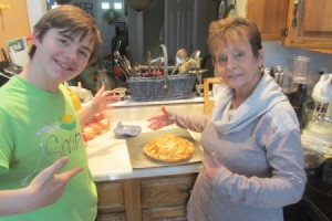A grandmother and grandson proudly showing off their Pi Day pie.