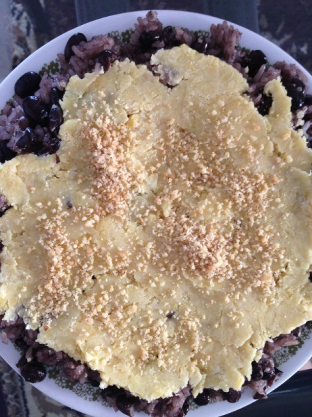 sticky rice and beans in bowl with coconut cream and chopped nuts