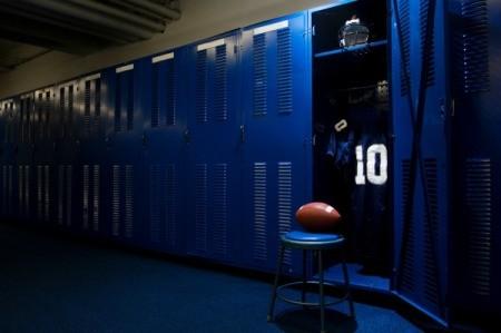 A football locker room with blue lockers.