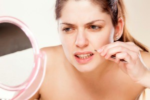 A woman removing hair from her upper lip.