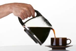 A hand pouring coffee into a cup.