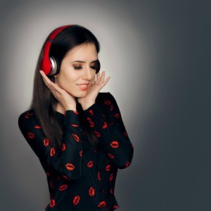 A woman listening to music on red headphones.
