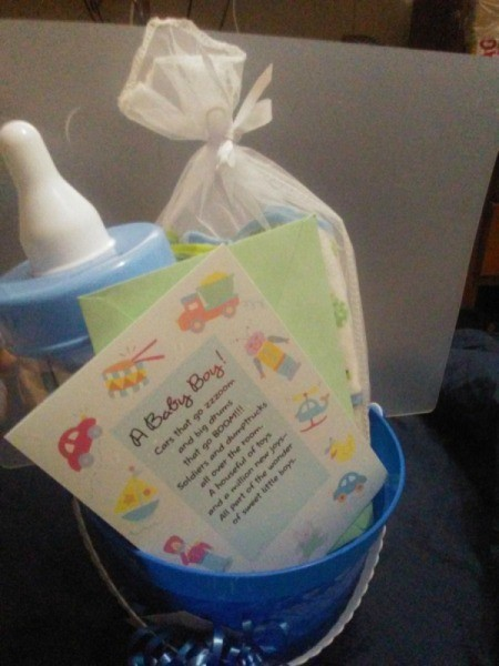The contents of a baby shower gift, placed in a reusable pail.