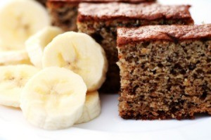 A slice of banana cake next to sliced bananas.