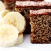 A slice of banana cake next to sliced bananas.