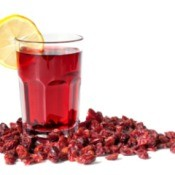 A glass of cranberry juice surrounded with cranberries.