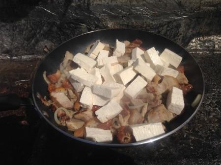 Adding tofu to the stir fry pan.