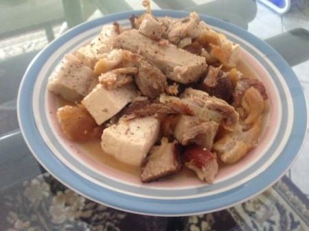 A plate of tofu and pork belly stir fry.