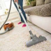 A woman cleaning a carpet in front of a door and couch.