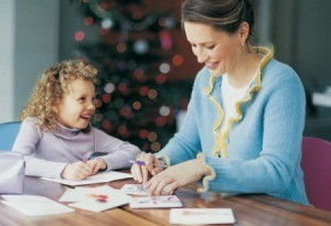 A woman and girl writing Christmas cards.