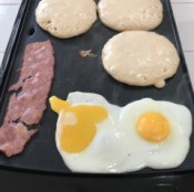 pancakes, bacon and eggs on an electric griddle.