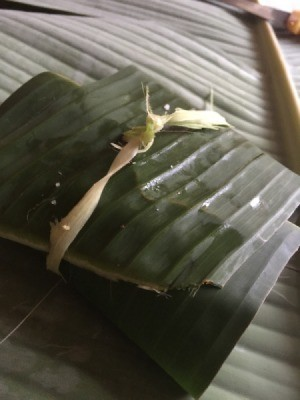 wrapped small fish in tied  banana leaf