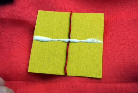 Birthday Parcel Card - apply glue to stick on bow, across the first piece of cord