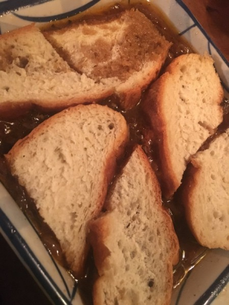 adding bread sliced to broth in pan for French onion soup.