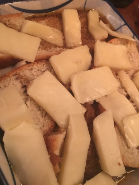 cheese slices on bread in pan for French onion soup.