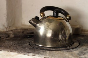 An old metal tea kettle on a stove.