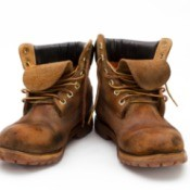 A pair of well worn work boots, on a white background.