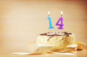 Birthday cake with burning number fourteen candle