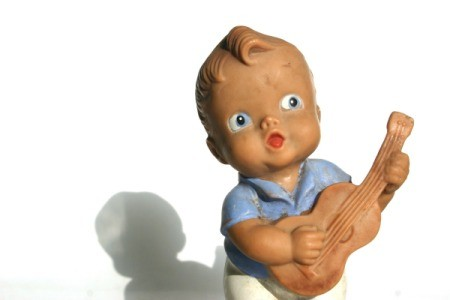 Old rubber doll of a boy playing a guitar.