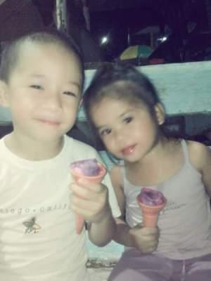 Two children eating ice cream cones.