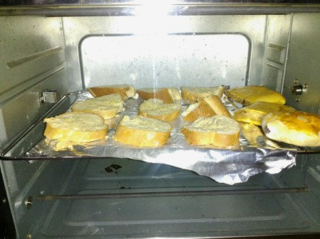 garlic bread pieces on foil lined pan in oven