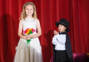 A boy and girl performing a magic show.