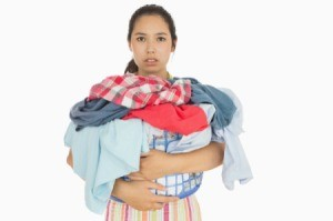 A woman holding a basket full of laundry.