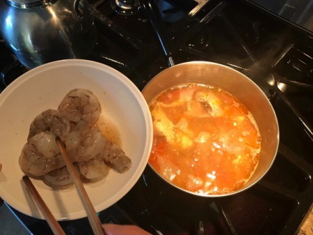 shrimp being added to soup