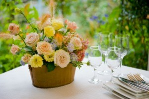 Cheerful bouquet on white table cloth next to place settings.