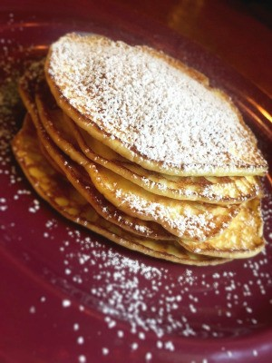 Mini Cream Cheese Crepes on plate and sprinkled with powdered sugar