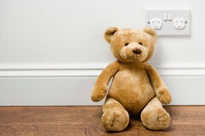 Teddybear sitting next to a childproofed outlet.