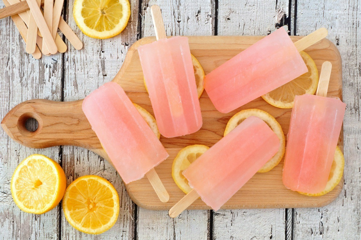 Pink popsicles on a wooded cutting board with slices of lemon. Kool-aid ...
