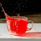 Cup of Kool-Aid splashing out onto the table.