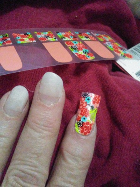 Placing nail decals on acrylic nails.