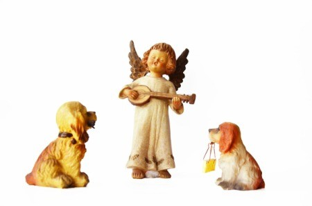 An angel figurine with two dog figurines.