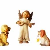 An angel figurine with two dog figurines.