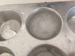 Ice cubes made in a metal muffin tin.