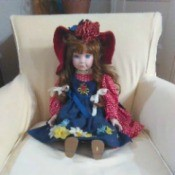 Value of a Porcelain Doll - doll wearing a red and blue pinafore dress and hat