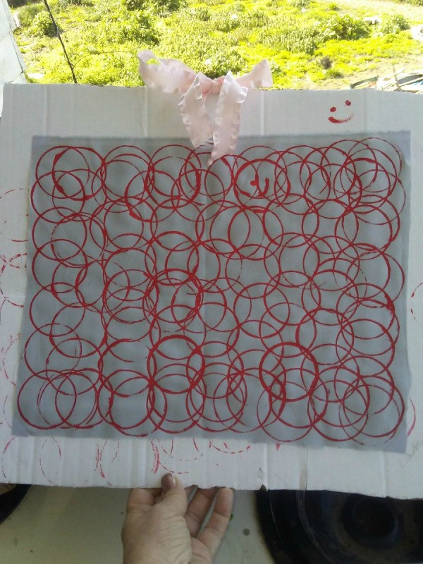 Fabric Stamp Art - white fabric with red overlapping paint circles mounted to a piece of cardboard